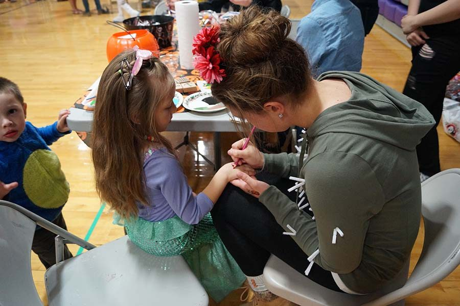 One school Halloween tradition is the Pied Piper Pumpkin Patch. Junior Grace Haworth paints a young participants' hand.