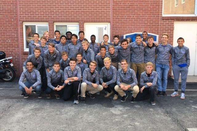 The boys' soccer team poses wearing their new  pullovers. A donor provided funds for the jackets, which prompted the team to volunteer and pay it forward.