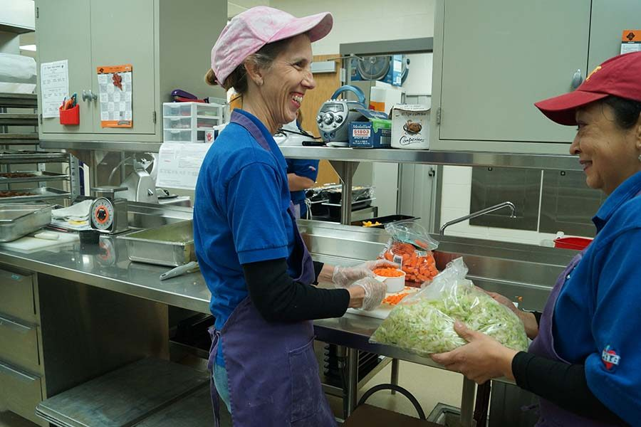 Christine Textor smiles as she cooks with her coworker.