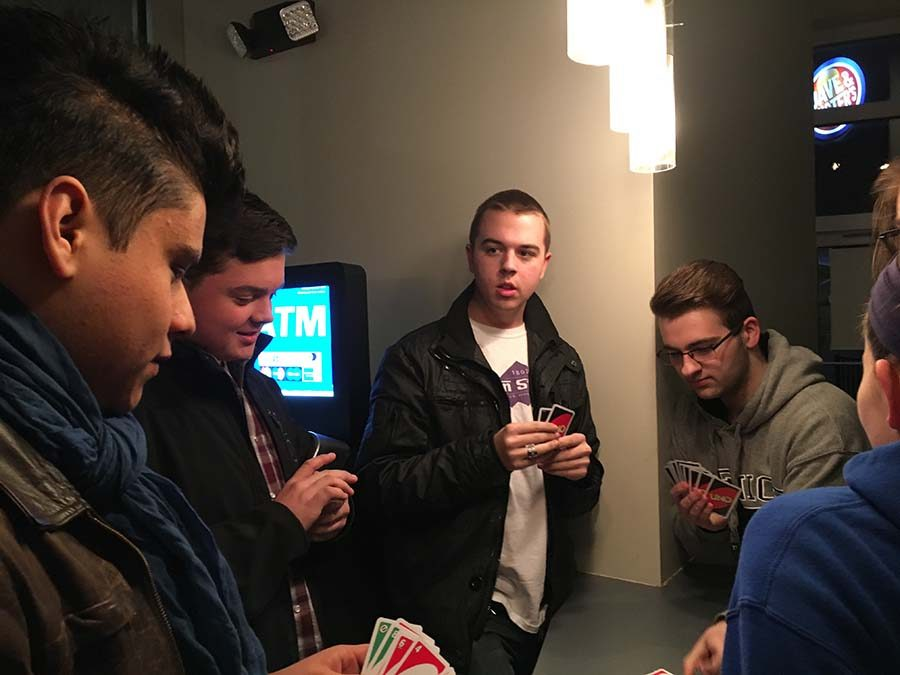 Alvarez and friends play a card game to relax before the show begins.