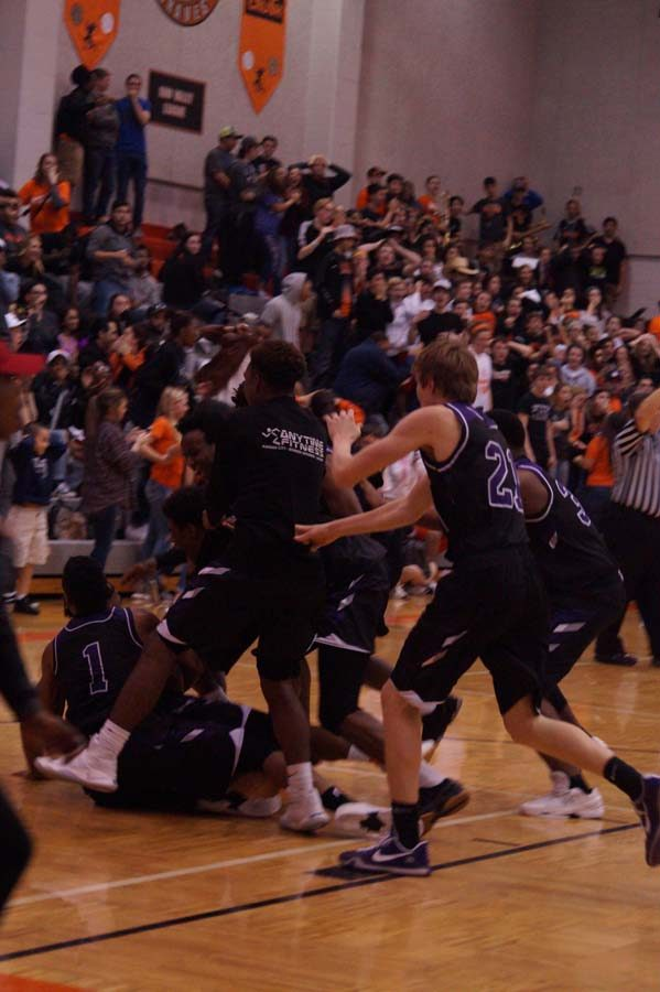 The Varsity boys pile up in celebration of the half-court shot by Letcher that won the game for the pirates with a score of 74-73.