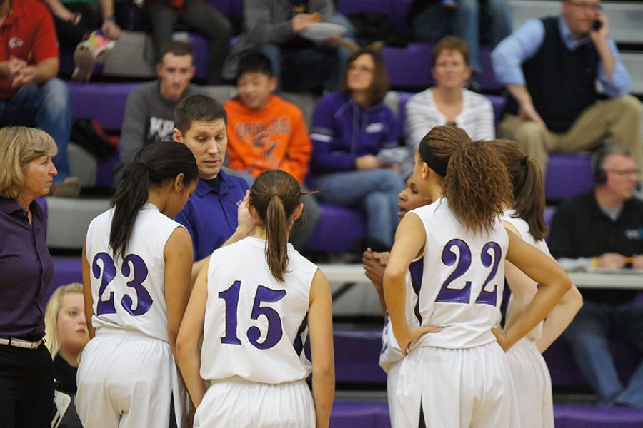 Members of the girls varsity basketball team listen to coach Shane Stouts advice during the season opener against Ottowa Dec. 2.