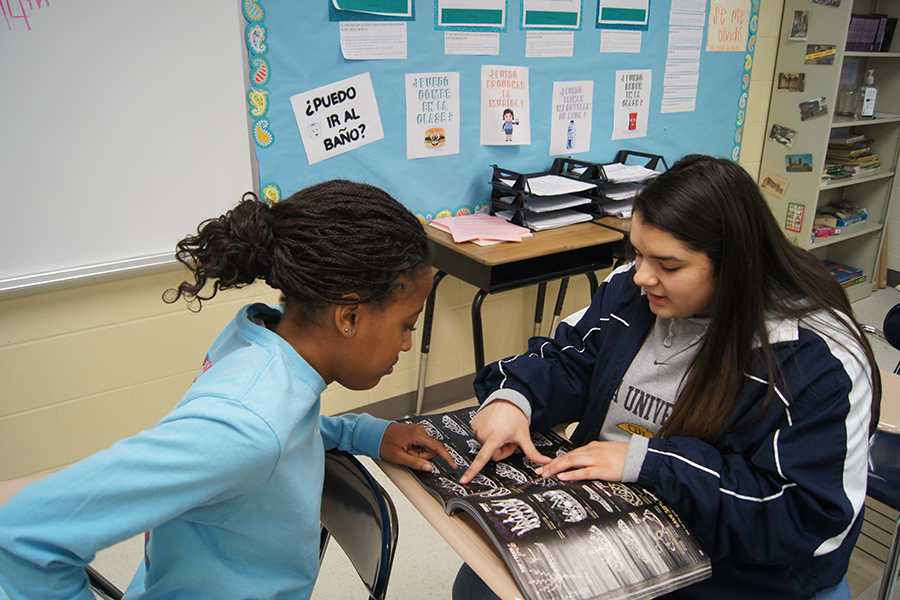 "Juniors Keisha Jones and Rachel Bertrand look through catalogs for crowns for prom royalty.  ""I am excited to see how everything comes together for Prom,"" Bertrand said. ""We have worked hard and I think it will look great."""