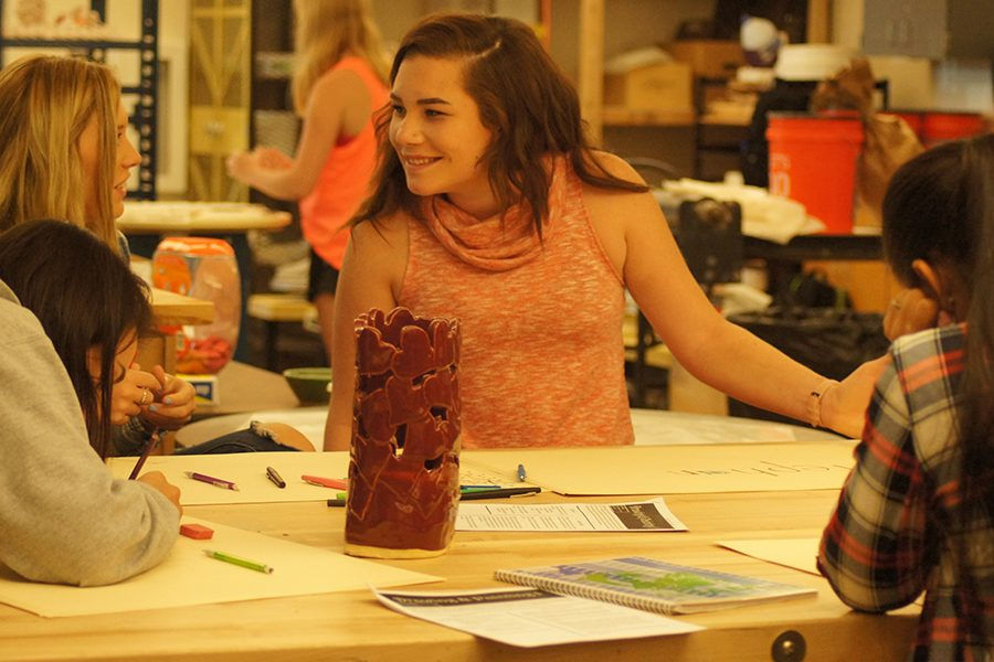 Senior Stephanie Michael consults with a friend during drawing and painting class Aug. 16