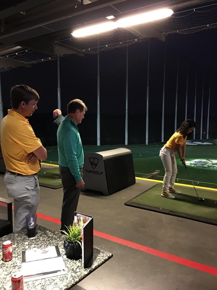 Do receives a golf lesson from Watson at Topgolf.