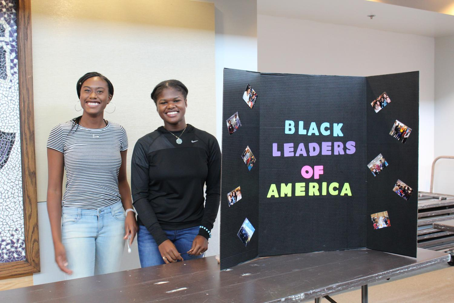 Two+students+involved+with+Black+Leaders+of+America+set+up+a+display+to+encourage+others+to+sign+up+for+the+organization.