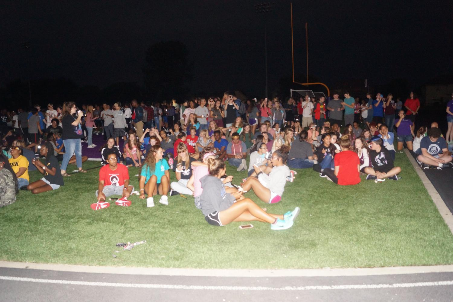 Students and teachers look around at the sudden darkness caused by the solar eclipse.
