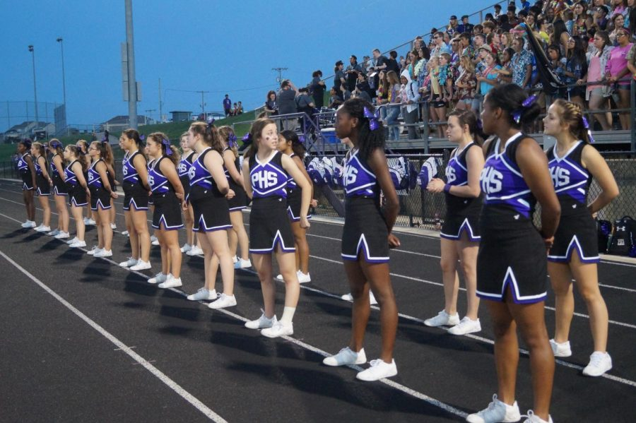 Cheerleaders watch the game as they prepare for the next chant.