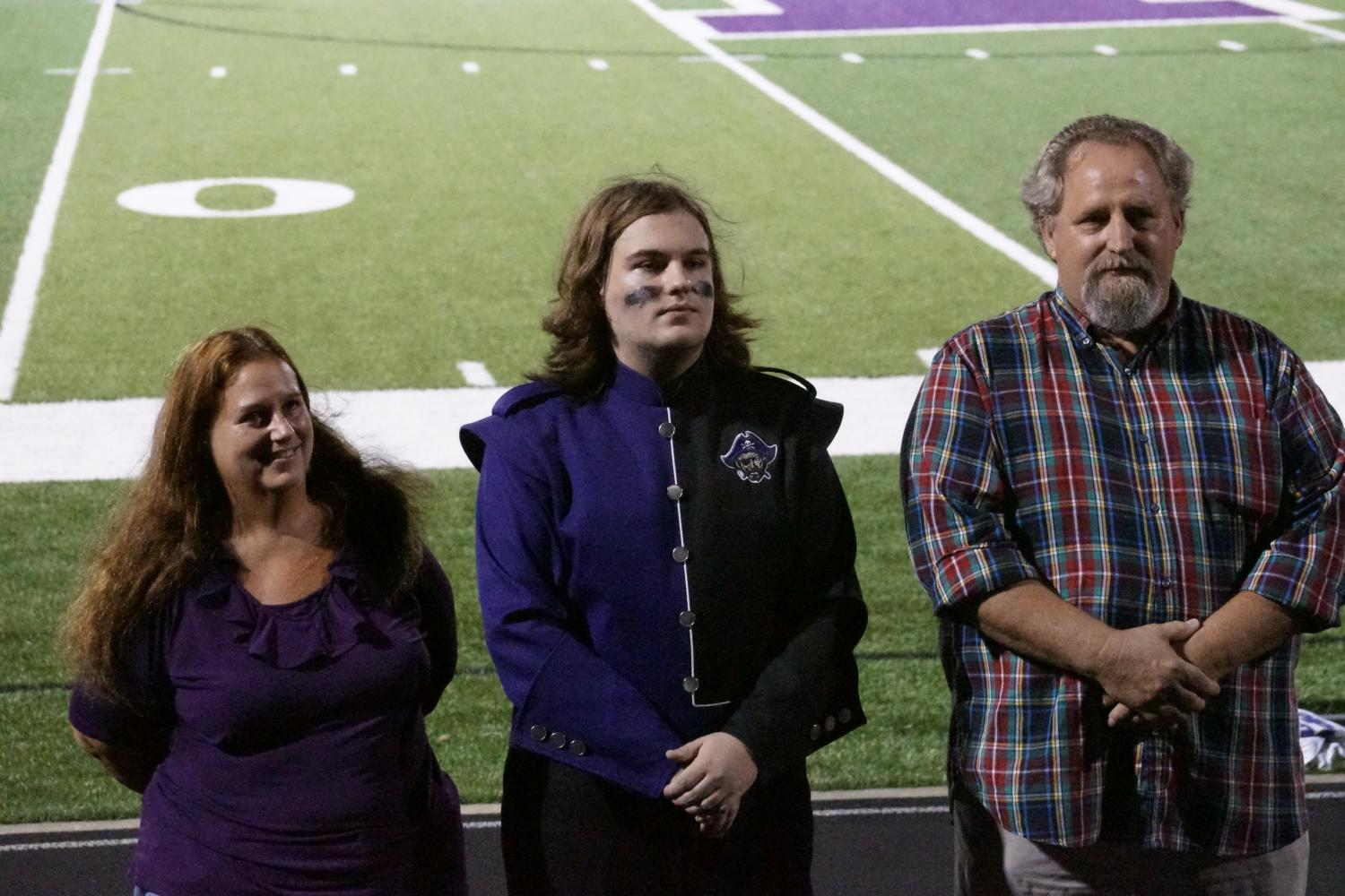 Senior Michael Gentry stands next to his parents on the field as he is recognized as a commended National Merit Scholar.
