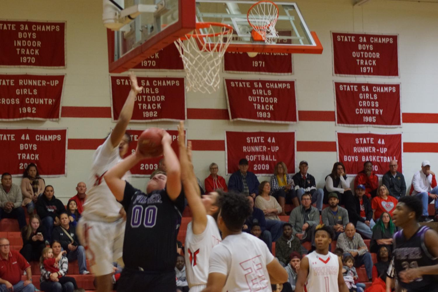 Junior Cooper Beebe shoots a layup during a game versus Ottowa on Dec 1. Beebe said that playing basketball himself helps him referee for younger kids.