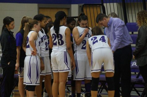 Coach Stout goes over the plays with the girls during the time out.