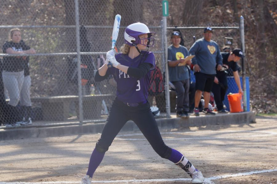 Senior Emma Golden is up to bat, digging her foot into the plate as she takes a swing.