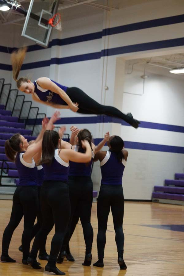 Sophomore Morgan Haworth twists through the air as her teammates prepare to catch her.