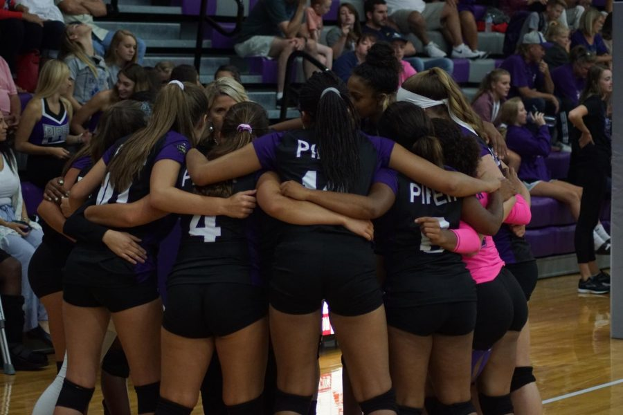 The varisty volleyball squad huddles up during a timeout by Coach Swatek.