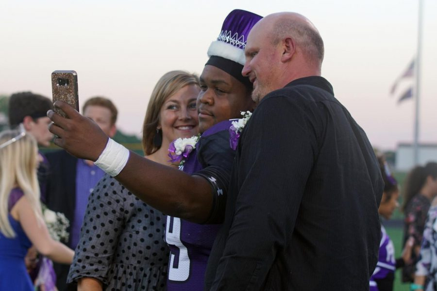 White poses with his parents for a selfie after he wins Homecoming King.