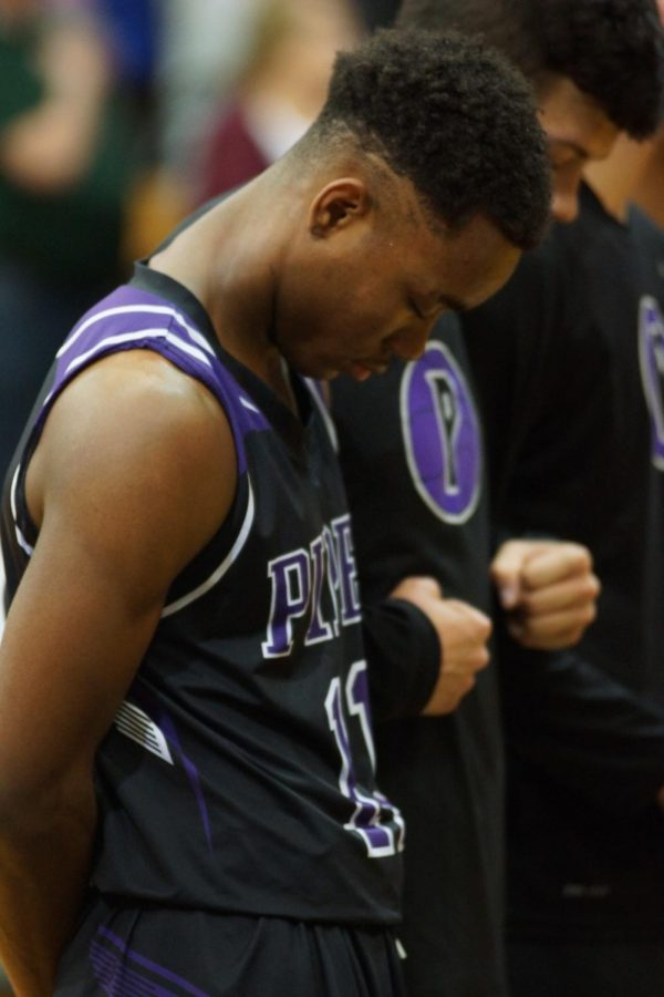 Senior Trey Bates bows his head during the national anthem during last years sub-state game at Basehor-Linwood