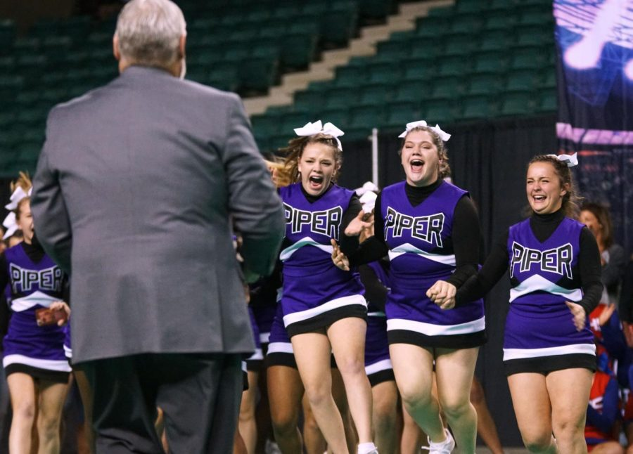 Juniors Courtney Johnson, Emma Vogel and Sydney Rhodes rush towards the trophy as the Pirates are announced as the 2018 Cheer State Champions Nov. 17.