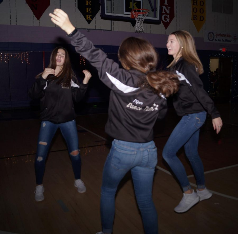 Piper Dance team members dance together as one of their favorite songs play. These three freshman have a close relationship and love dancing together.