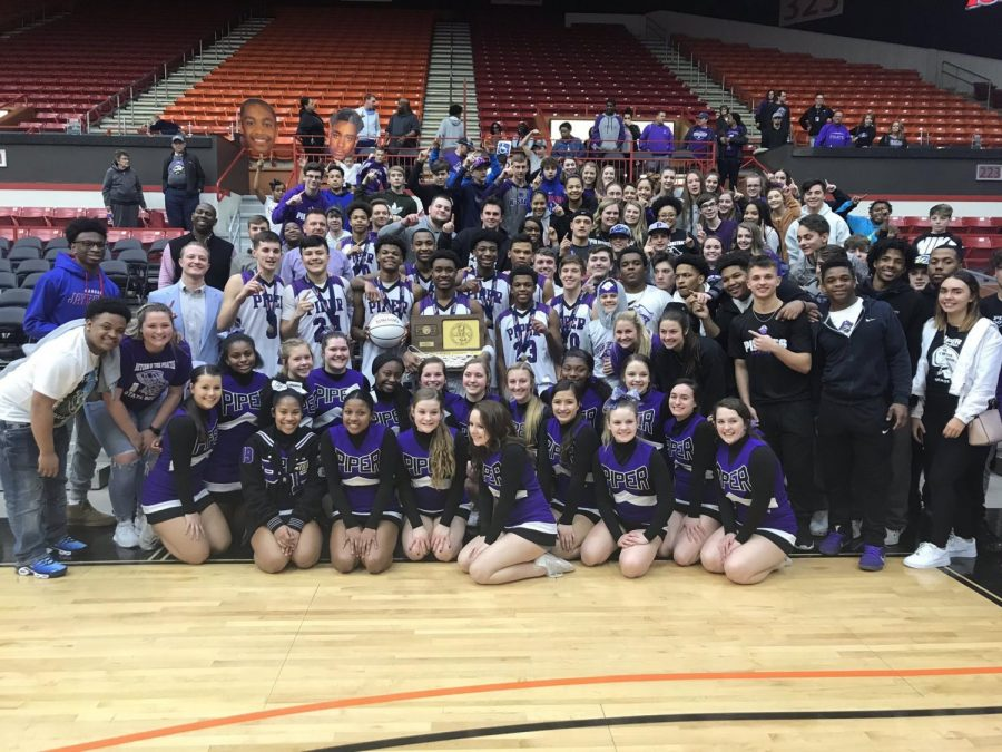 The boys basketball team poses with their first place trophy with fans and cheerleaders after defeating Augusta.