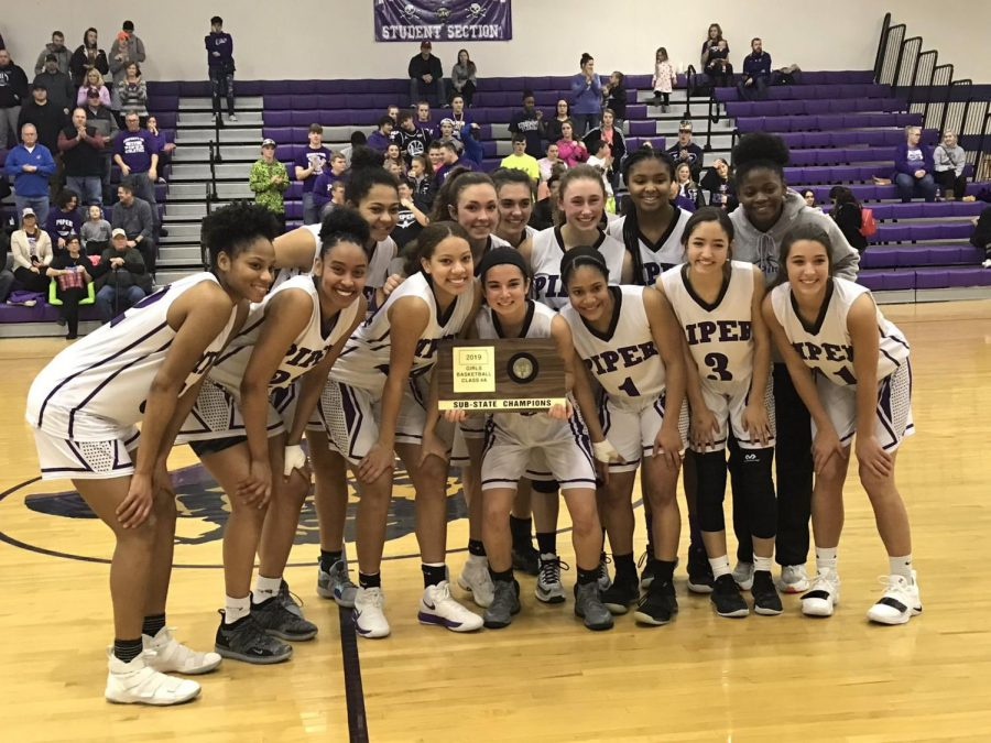 The Lady Pirates pose with sub-state trophy after defeating Chanute.