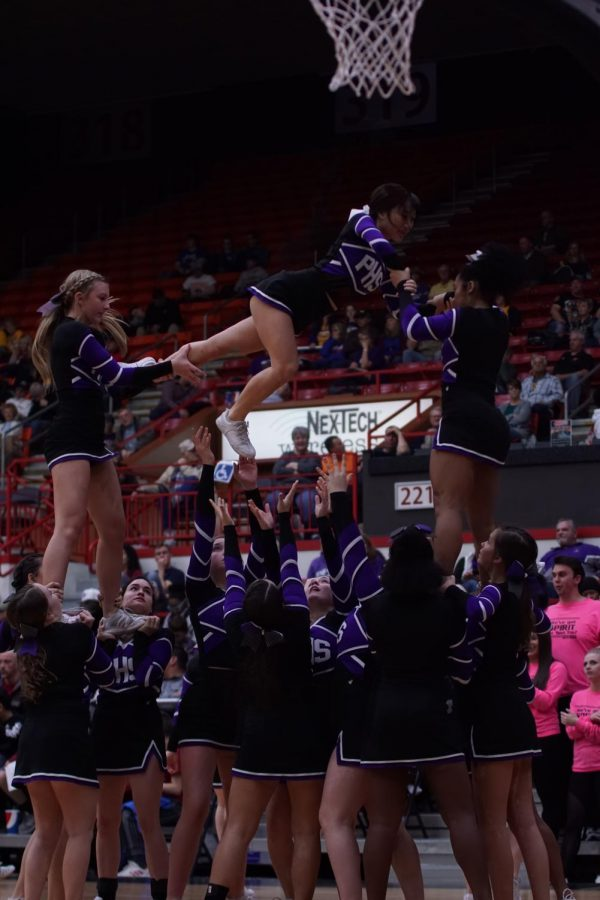 The cheer team performs a stunt during a timeout at the state basketball tournament.