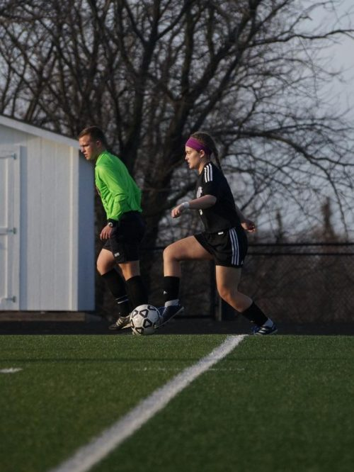 Junior Emily Brandt dribbles the ball in the game against Atchison.