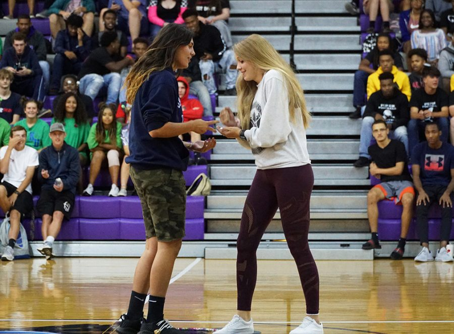 Senior Ali Vigil and freshman Shalom Searcy compete against one another in a rock paper scissors race. The Homecoming pep rally had many games for students to participate in.