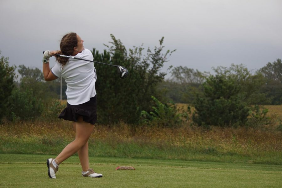 Senior Sydney Rhodes drives a ball towards to the green. Rhodes qualified for state and will be competing Oct. 21.
