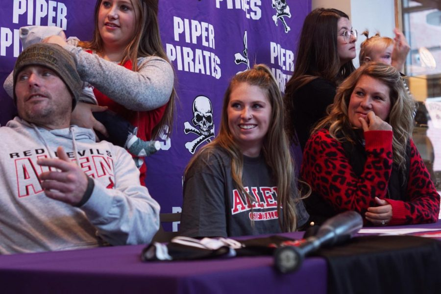 Senior Bella Gravatt shares a laugh with her sisters as her family joins her at her signing. Gravatt will be playing middle infield at Allen County Community College.