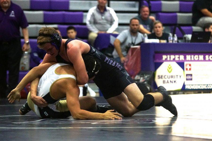 Junior Branden Martin pins his opponent at the Piper meet.