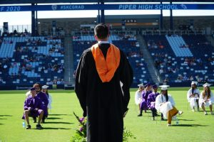 Graduates walk the stage at socially distanced graduation nearly three months later than planned