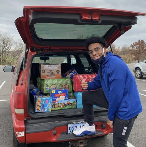 Senior Arrick Taylor poses in front of trunk full of snacks for Pirates Bay.