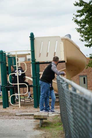 Fine arts teacher Randy Robertson stands next to playground during cohort break.