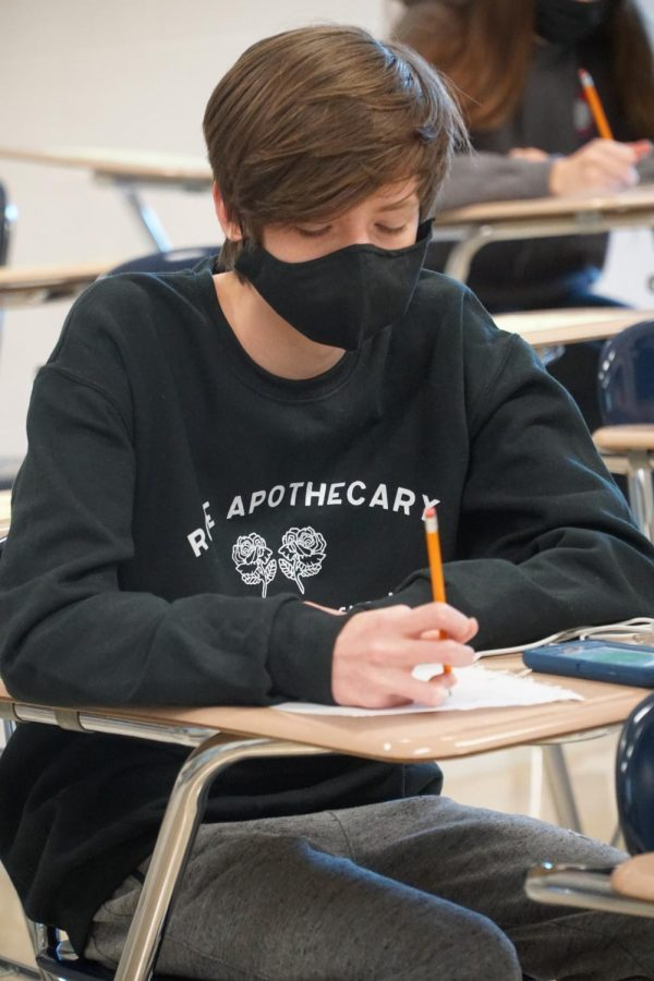 Freshman Jack Wells writes on a piece of paper during a Scholars Bowl meet.