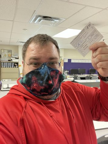 High School teacher Stephan Brumbaugh poses with vaccination card which shows receipt of receiving the COVID-19 vaccine.