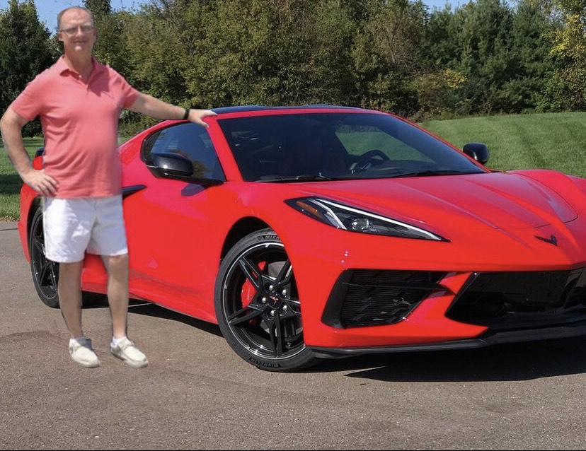 Chris Brindle poses with a photoshopped red sports car. This photo is one of many that is posted on @iheartbrindle.