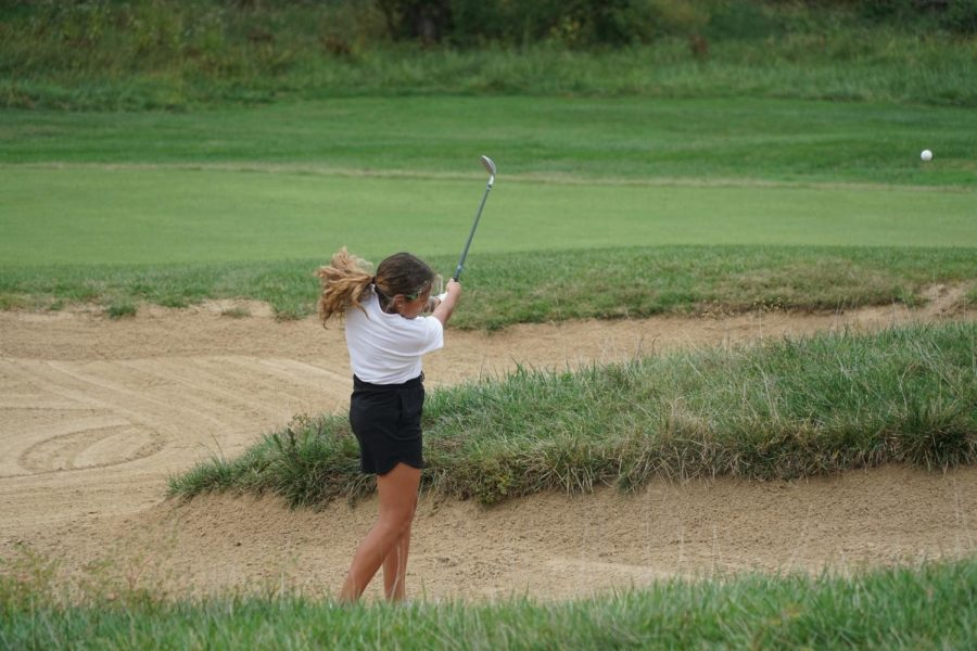 Sandy situation: Junior Tatum Vallejo, hits the ball out of a sand pit at the Falcon Lakes meet.