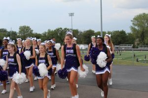 Cheerleaders cheer on the crowd while walking the parade route.